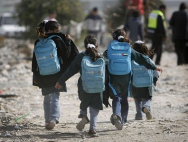Children run through rubble on their way home from school in east ...
