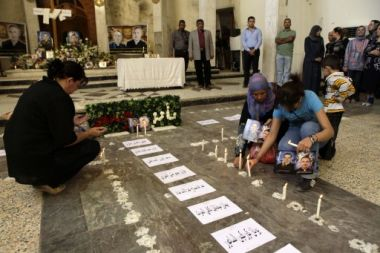 A Christian woman prays, left, as Muslims light candles, right, for ...