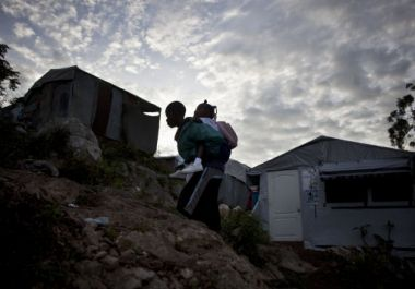A boy carries a girl to school at a camp for earthquake displaced ...