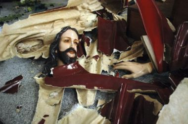 A statue of Jesus Christ is left smashed on the floor of a church ...
