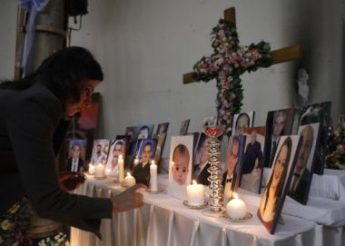 A woman lights a candle among pictures of slain Iraqi Christians at ...