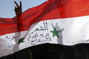 Syrian expatriates gesture as they hold a Syrian national flag during ...