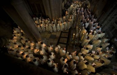 Catholic clergy walk holding candles during a procession inside the ...