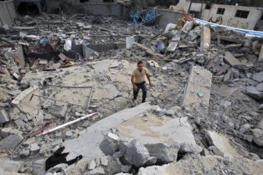 A Palestinian walks through the rubble of the house of Issam Al ...