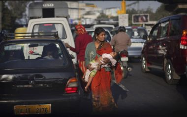 This 21 December photo shows an Indian woman carrying her baby as she ...