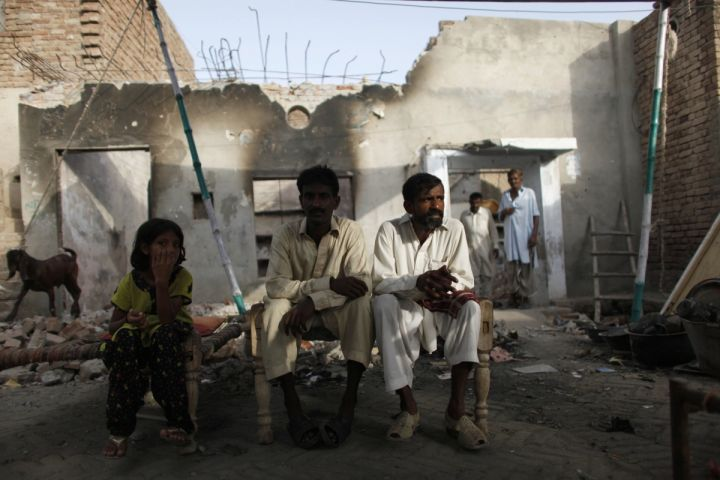 A Christian family rests in front of their destroyed house