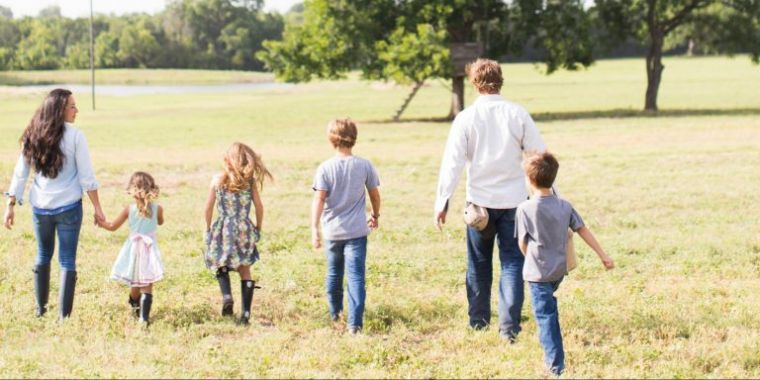 Chip and joanna gaines of fixer upper walk on a grassy field