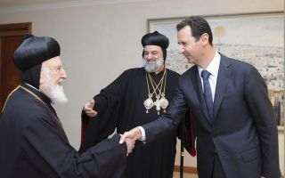 his-holiness-ignatius-aphrem-ii-patriarch-of-the-syriac-orthodox-church-centre-shakes-hands-with-syrias-president-bashar-al-assad-before-a-meeting-in-damascus-in-2014