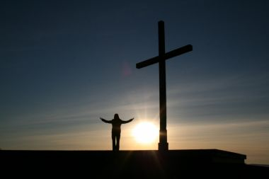 Beside a cross on hill at sunset