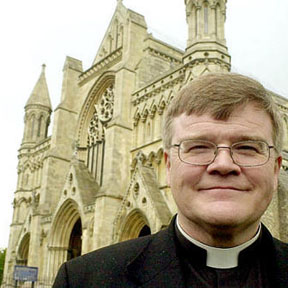 Dr. Jeffrey John poses outside St Albans Cathedral.