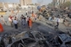 People gather at the bombing scene in front of the Iraqi Foreign ...